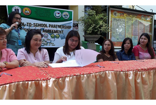 CES/OIC SDS Dr. Lualhati O. Cadavedo (center) signs the School-to-School Partnership Agreement as witness together with participating schools' PTA presidents during the activity hosted by the Schools Division.